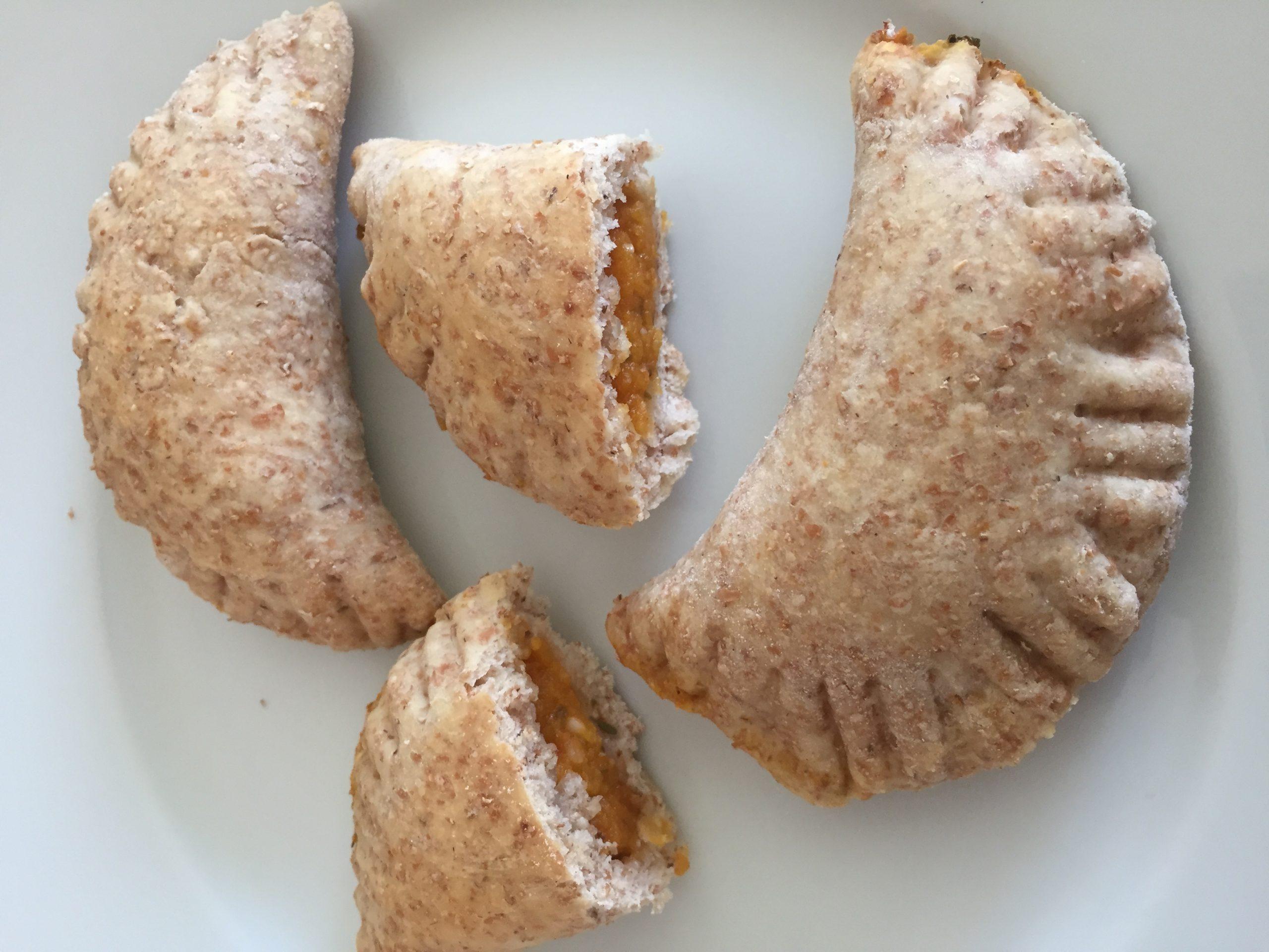Panzerotti dorati al forno con farina integrale e ripieno di zucca e pomodorini